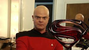 Rainn Wilson, bald, in a StarFleet Uniform, holding the Superman shield on a staff