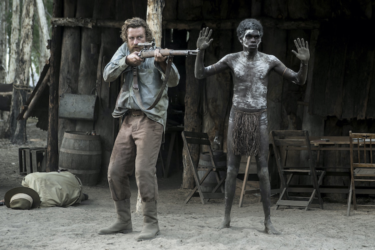 [L-R] Simon Baker as Travis and Jacob Junior Nayinggul as Gutjuk in the adventure/drama film, HIGH GROUND, a Samuel Goldwyn Films release. Photo Courtesy of Samuel Goldwyn Films.