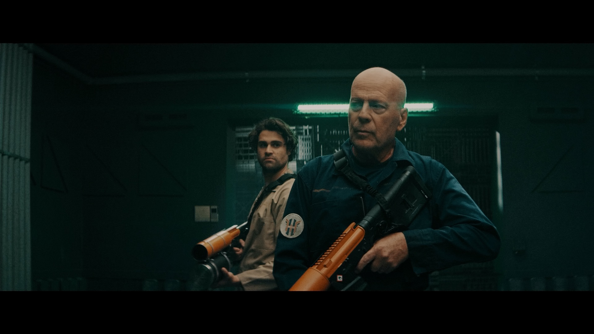 (L - R) Cody Kearsley as Noah and Bruce Willis as Clay Young in the sci - fi/action film, BREACH , a Saban Films release. Photo courtesy of Saban Films